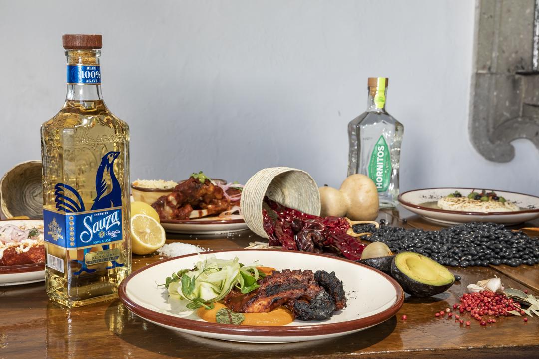 platillo en mesa con tequilas e ingredientes sauza reposado y hornitos
